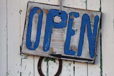 Image of open sign on wooden door representing companies in Asia being open to engaging the global community of independent white hats