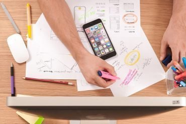 Image of entrepreneur with iPhone and drawing up plans representing privacy and data security mistakes for start-ups