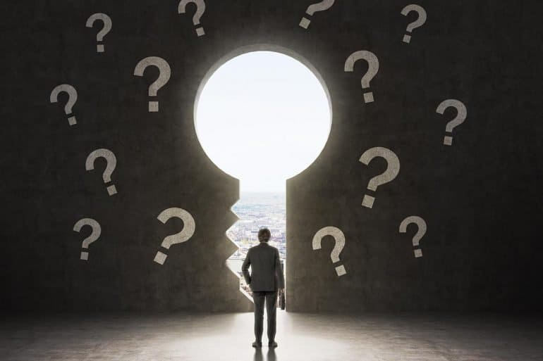 Image of man standing in from of keyhole with questions representing the unknowns in terms of development in Indonesian privacy rules