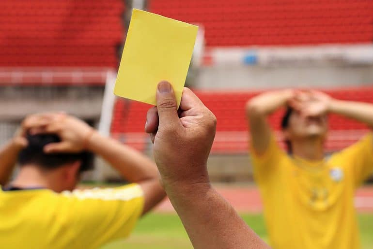 Image of referr giving yellow card to players representing tightening of Malaysia personal data protection standards