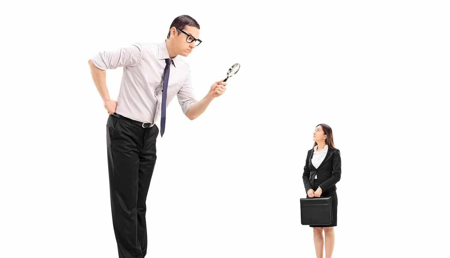 Image of big man using magnifying glass to scrutinize employee representing whether employers can find the employee privacy sweet spot