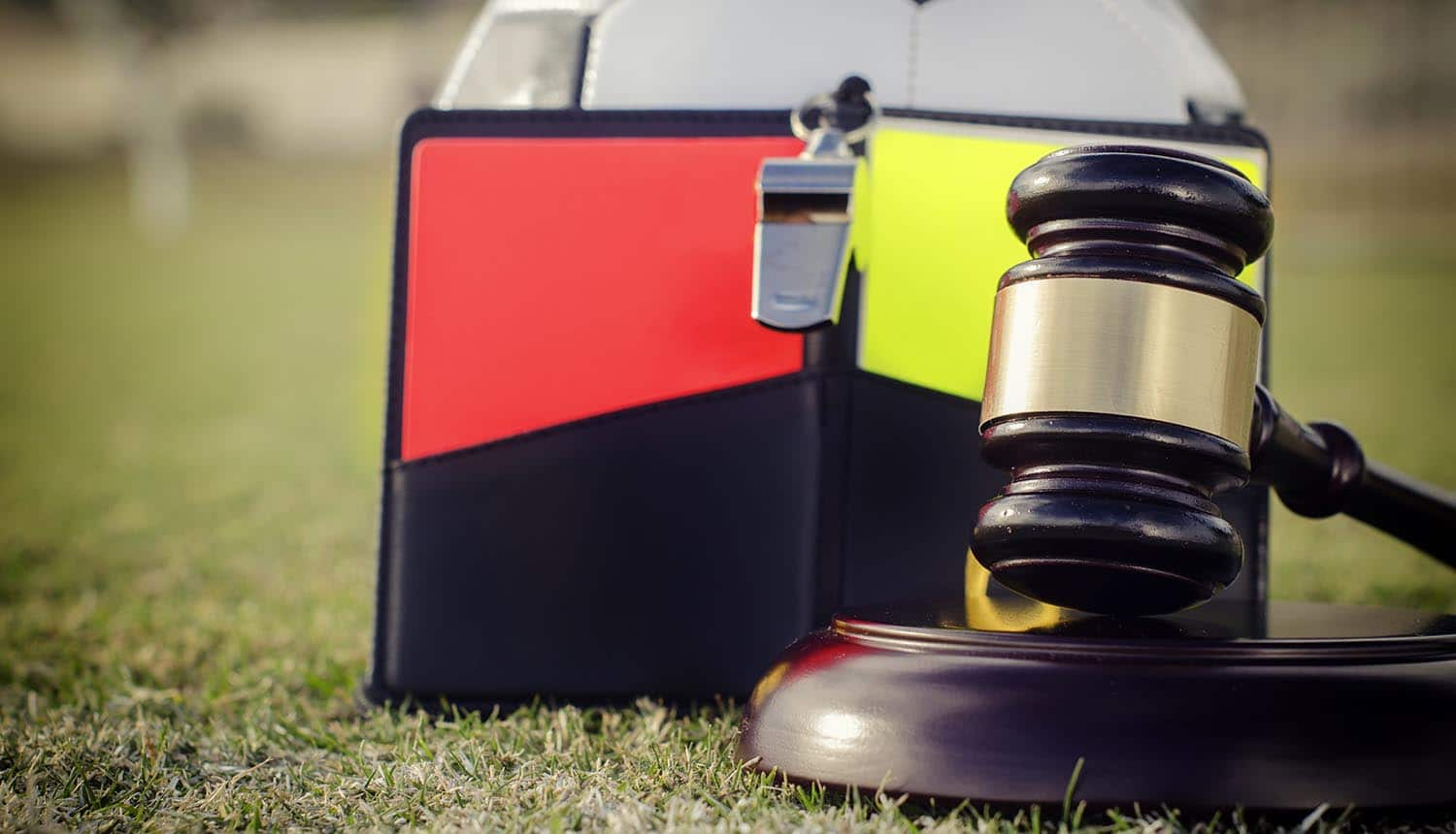 Image of hammer and gavel against backrop of soccer ball and red and yellow cards representing data protection