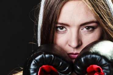 Image of woman wearing boxing gloves representing the fight in the recent U.S. vs Apple case