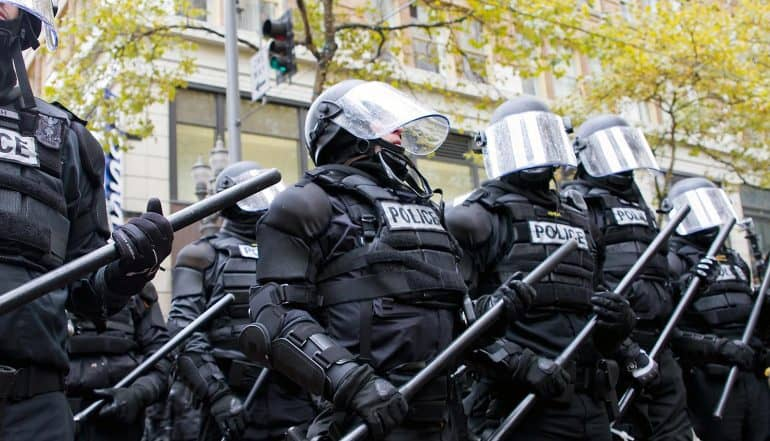 Image of police officers in riot gear representing government control in the context of the recent U.S. vs Apple case