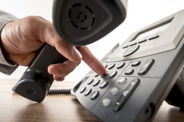 Image of man pressing buttons on desk phone representing the recent U.S. vs Apple case