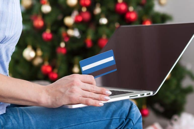 Image of woman holding credit card in front of laptop representing how online retailers are preparing for the holiday hacking season