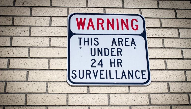 Image of warming sign on wall representing government surveillance and the consideration of security and privacy