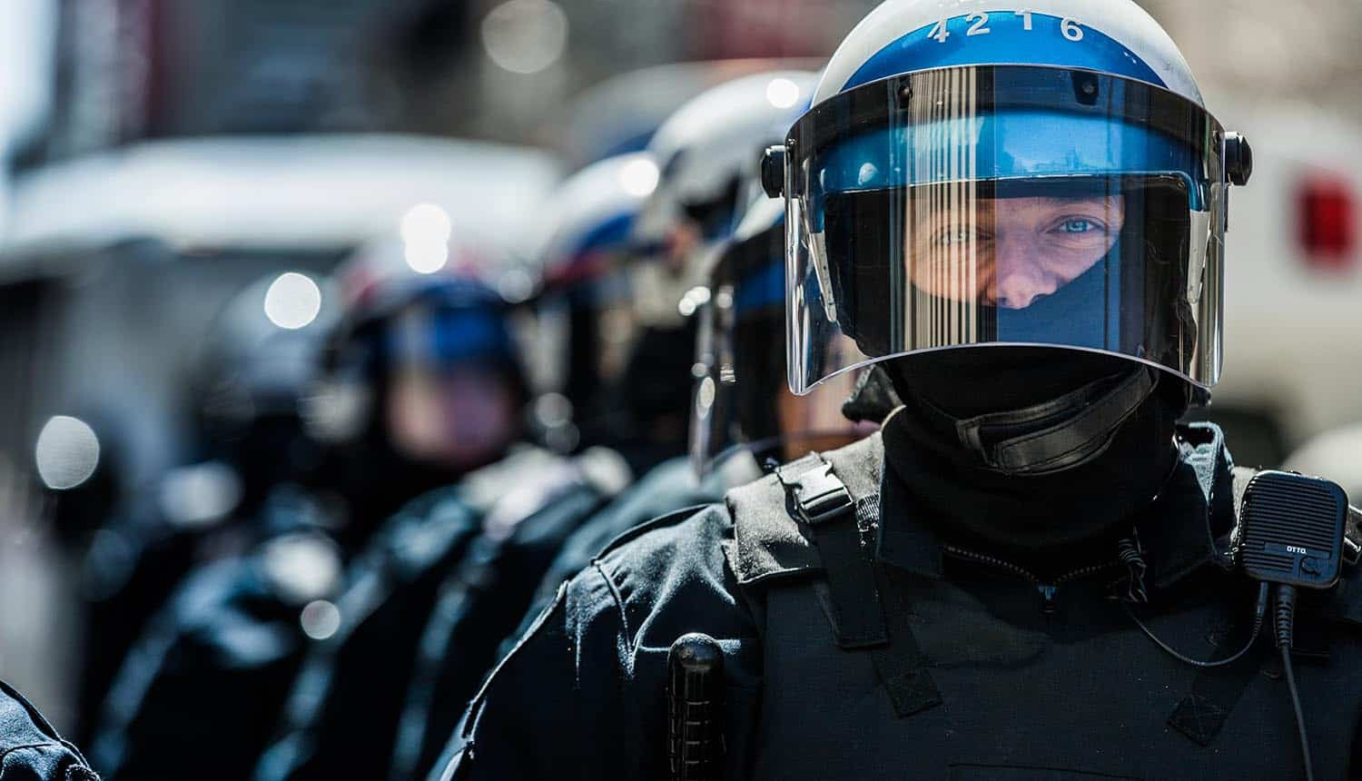 Image of police in riot gear representing government surveillance and the impact on security and privacy