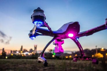 Image of drone flying towards city representing how ransomware is a threat to the internet of things