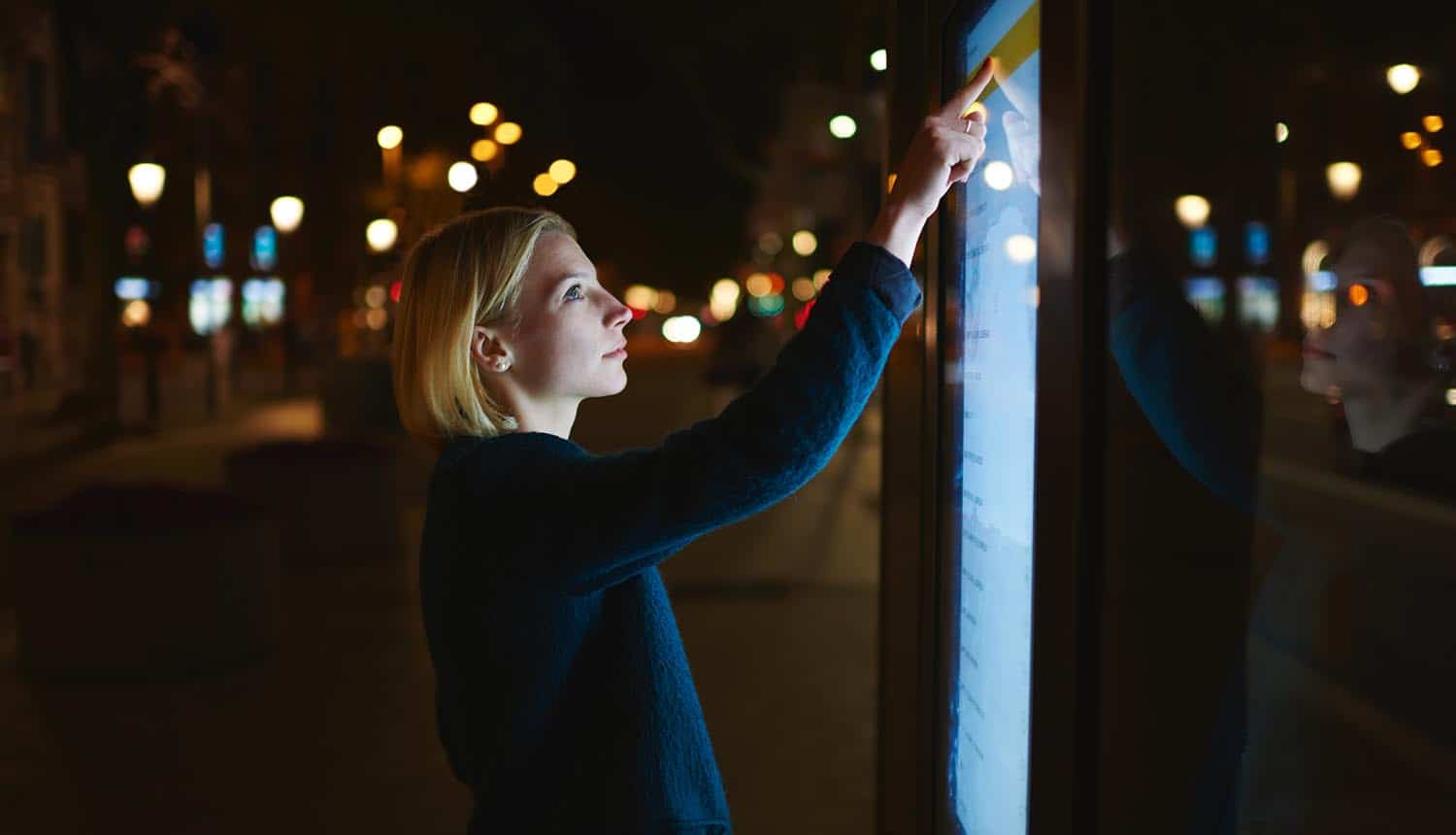 Image of woman using a giant screen in smart city representing the challenges faced by innovative enterprises in terms of big data privacy