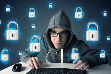 Image of hooded hacker in front of keyboard and surrounded by floating locks representing how to stop ransomware attacks