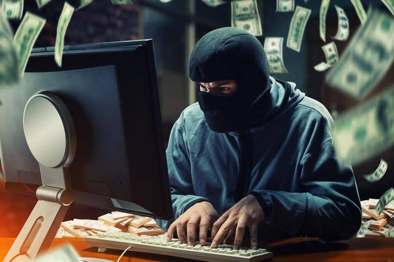 Image of hacker working on computer with money flying around representing how the FBI cyber crime report revealed that ransomware attacks are not as damaging