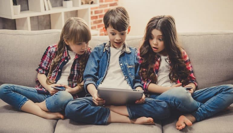 Image of kids with surprised look holding a tablet representing how Disney, the happiest place on earth, is facing problems for mobile apps for kids