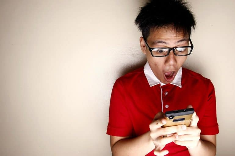 Image of man with surprised look holding mobile phone representing what is given away based on privacy policies and terms of use