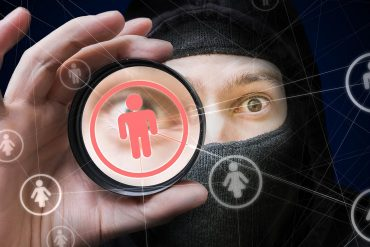 Image of hacker using lens on network of people icons representing why identity theft protection is necessary as shown by the Equifax breach