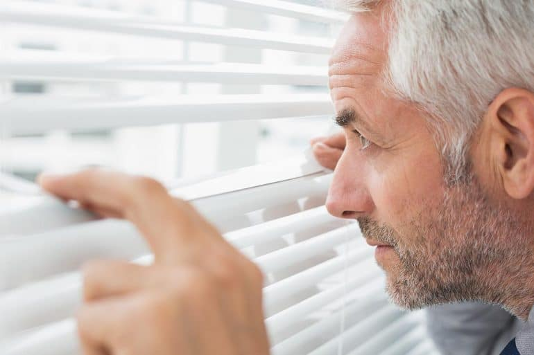Image of boss peering between window blinds representing the impact of the EU GDPR on privacy in the workplace