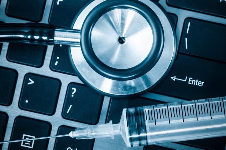 Image of stethoscope and syringe on laptop keyboard representing malware detection