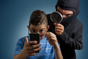 Image of hacker holding magnifying glass peering over shoulder of boy using mobile phone signifying the need to protect against identity theft