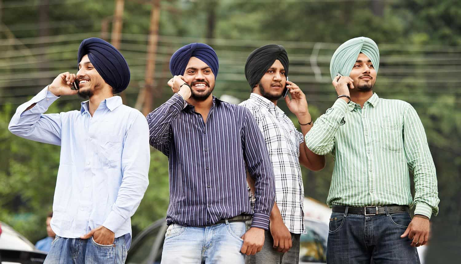 Image of Indians using their mobile phones representing cyber security standards mandated by the Indian government on phone makers