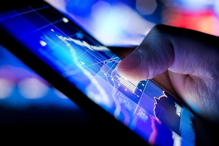 Image of hand holding mobile phone showing financial charts signifying the need for FinTech to protect the security and privacy of customer data
