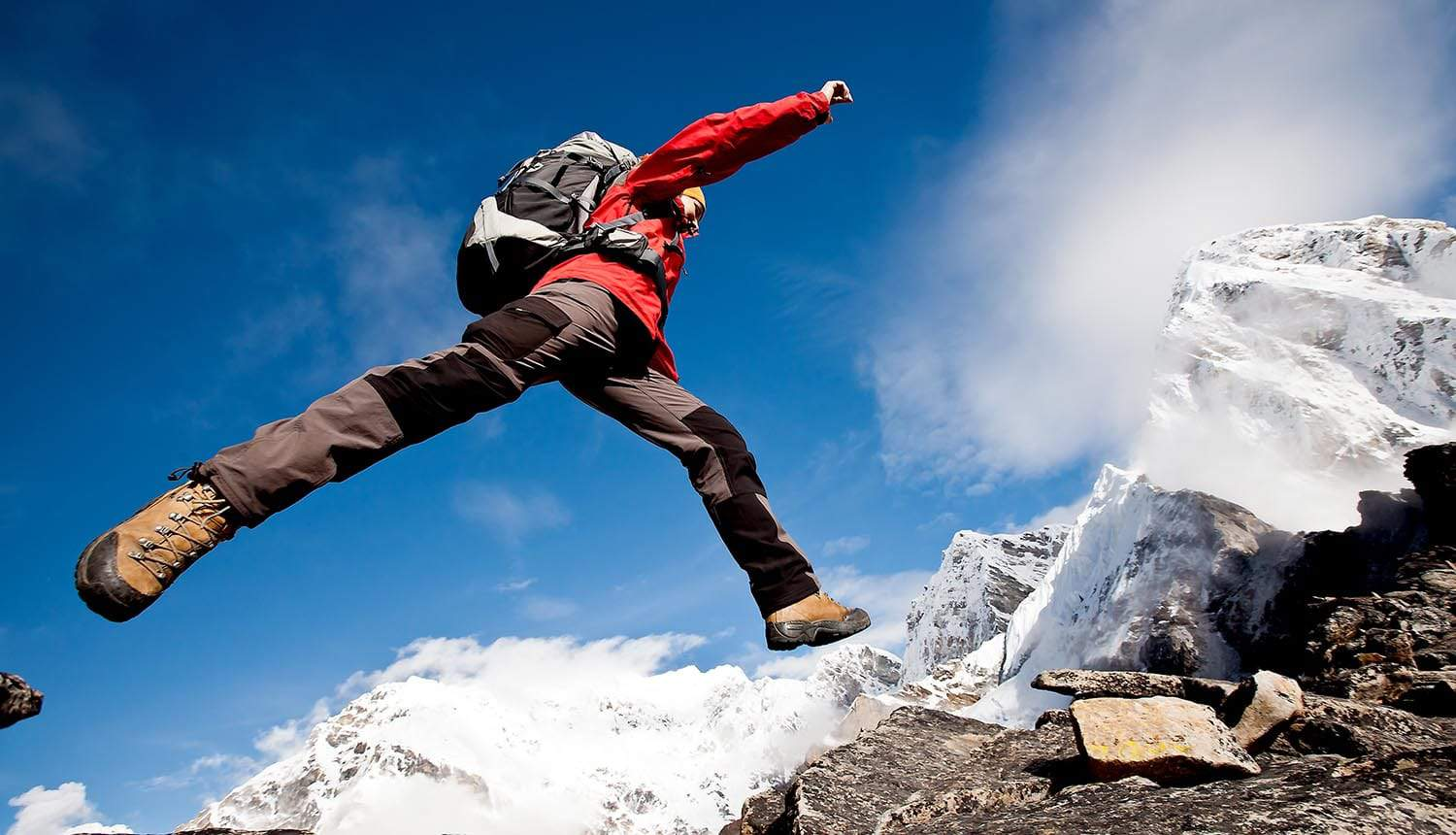 Image of man jumping over a crevice against moutain backdrop signifying how privacy professionals and CPO needs to bridge the gap and become security savvy as a CISO