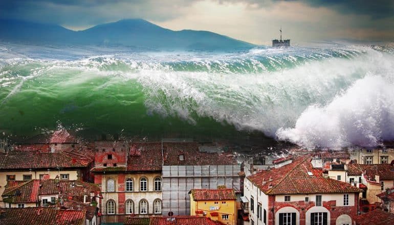 Image of a massive wave engulfing a city signifying the intensity surge in DDoS attack trend
