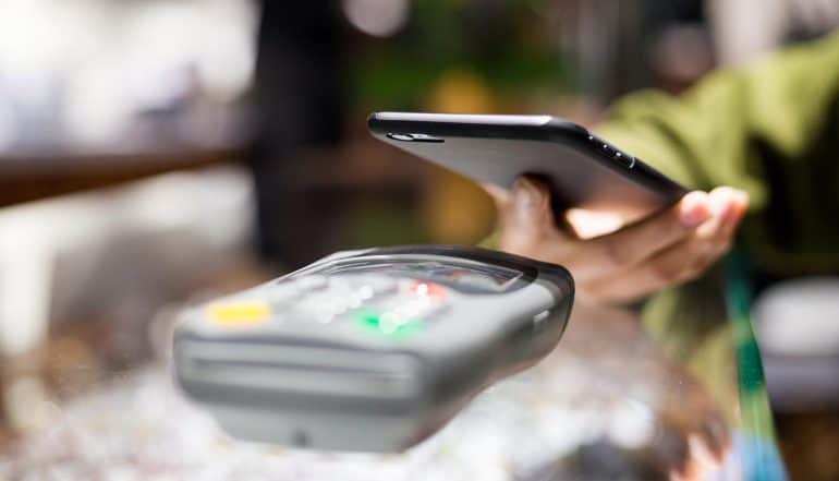 Image of shopper placing mobile phone on payment terminal signifying the questions of privacy implications in a cashless society