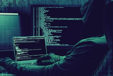 Image of hacker sitting in front of computer screens signifying cyber crime is facilitated by a growing underground market