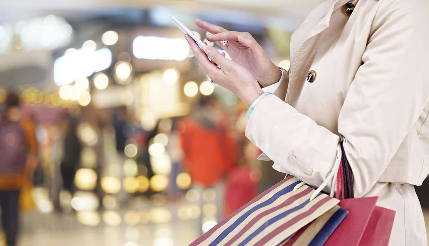 Image of female shopper using mobile phone signifying how retailers can boost consumer trust by offering identity protection for holiday shoppers