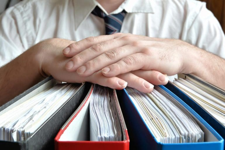 Image of businessman with hands resting on thick files representing protecting data subject rights for acccess, erasure and portability