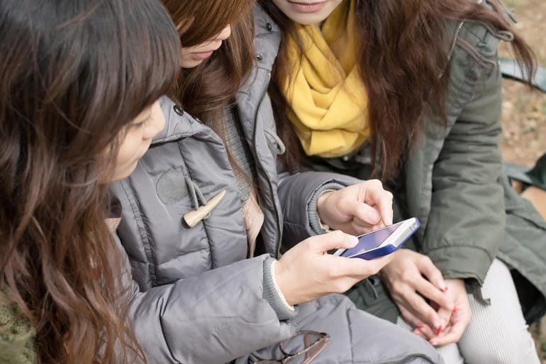 Image of group of girls looking at mobile phone representing changes in perception in customer privacy and digital trust