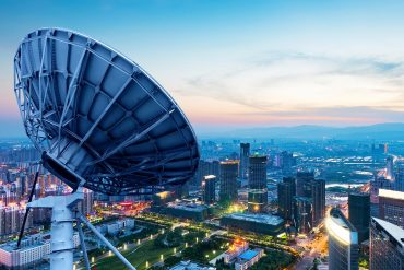 Image of satellite dish on rooftop overlooking a city representing China's social credit system