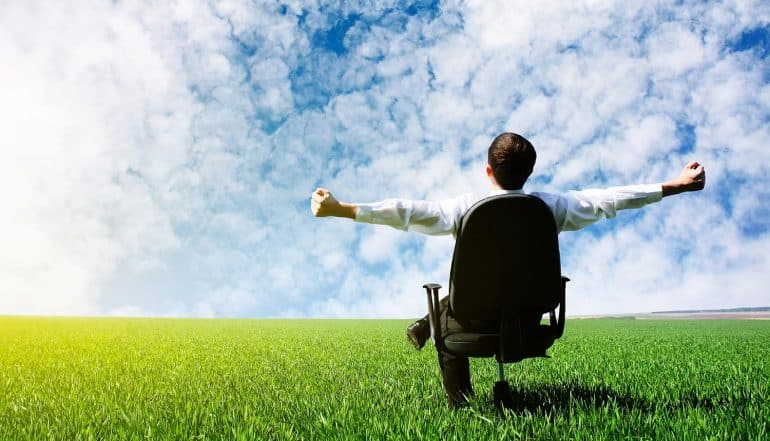 Image of businessman sitting in office chair with arms wide open looking at the sky representing businesses embracing cloud technology