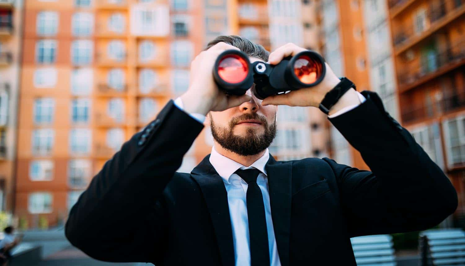 Businessman with binoculars spying on users, invasion of privacy by tracking online behavior