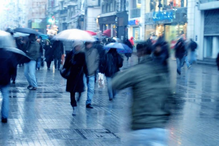 Image of busy street with people holding umbrellas in the rain representing identity protection