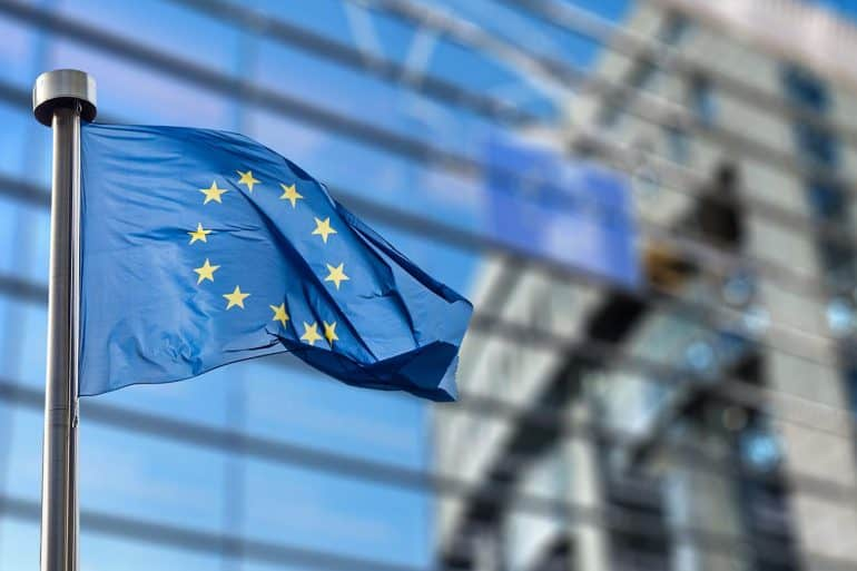 Image of European Union flag in front of a building signifying the consideration of consent under the EU GDPR and the requirements and recommendations for data controllers
