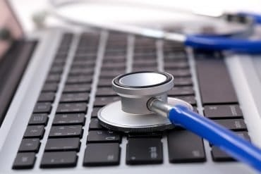 Image of stethoscope on laptop keyboard representing cyber risk benchmarking for cyber insurance
