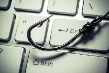 Image of fishing hook on keyboard representing phishing attacks using free phishing kits