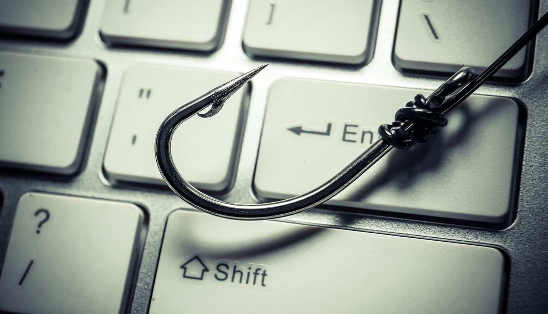 Image of fishing hook on keyboard representing phishing attacks using free phishing kits