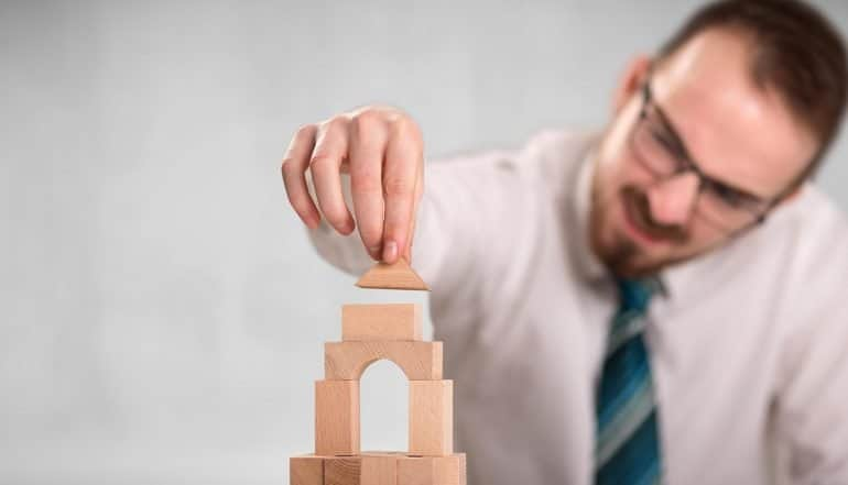 Image of man putting a block on a house model signifying a company starting up and buidling their first privacy program