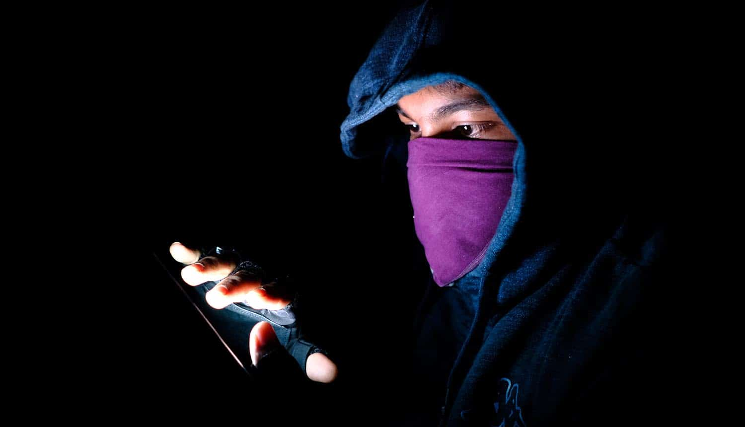 Image of hooded and masked man using a mobile phone signifying cyber espionage by hackers using fake apps with Android malware
