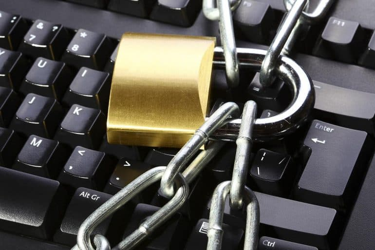 Image of lock and chain over keyboard signifying the need to protect the privacy of both home and business from ransomware