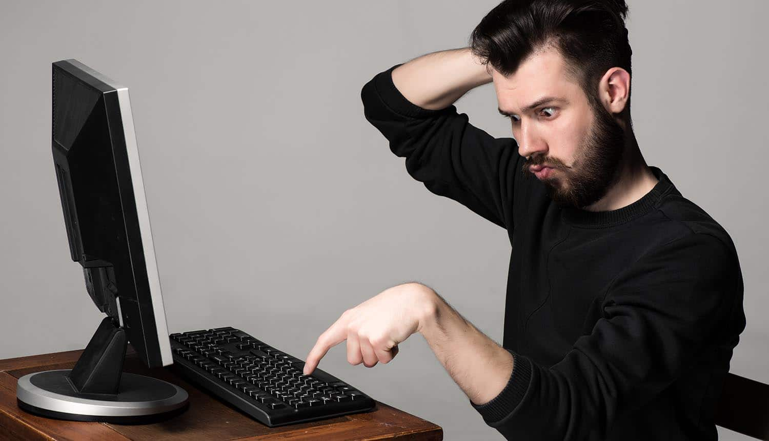Image of confused man sitting in front of computer about to type signifying insider threats within the organization