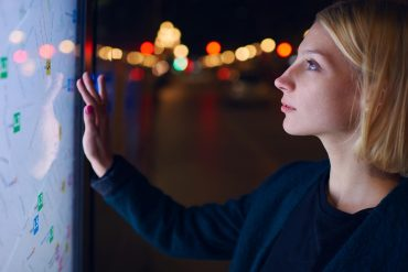 Image of woman standing in front of big screen and using it to find directions in smart city and the need for smart privacy