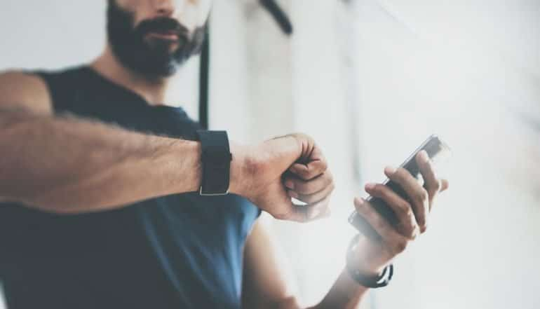 Image of man holding mobile phone with social fitness apps and looking at fitness wearable device and consideration for user privacy