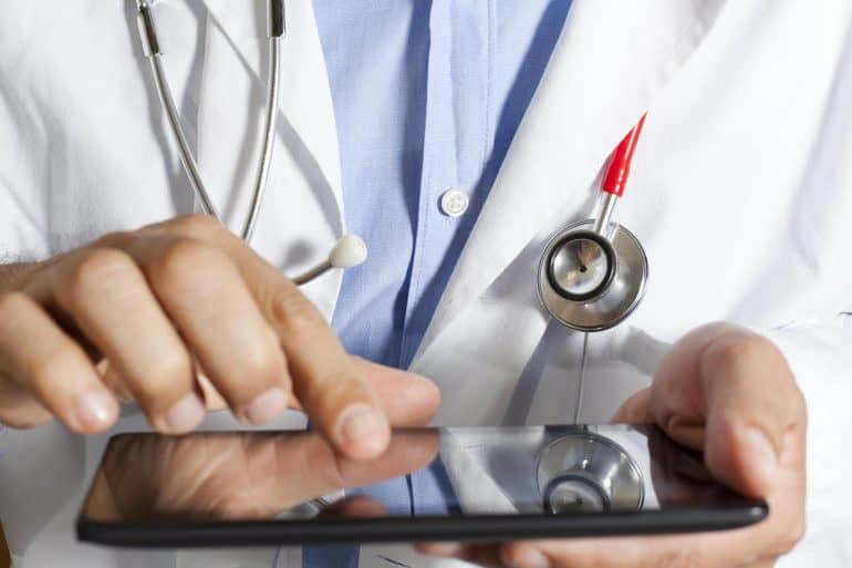 Image of doctor with stethoscope around neck and holding a tablet signifying the protection of information and privacy of the deceased