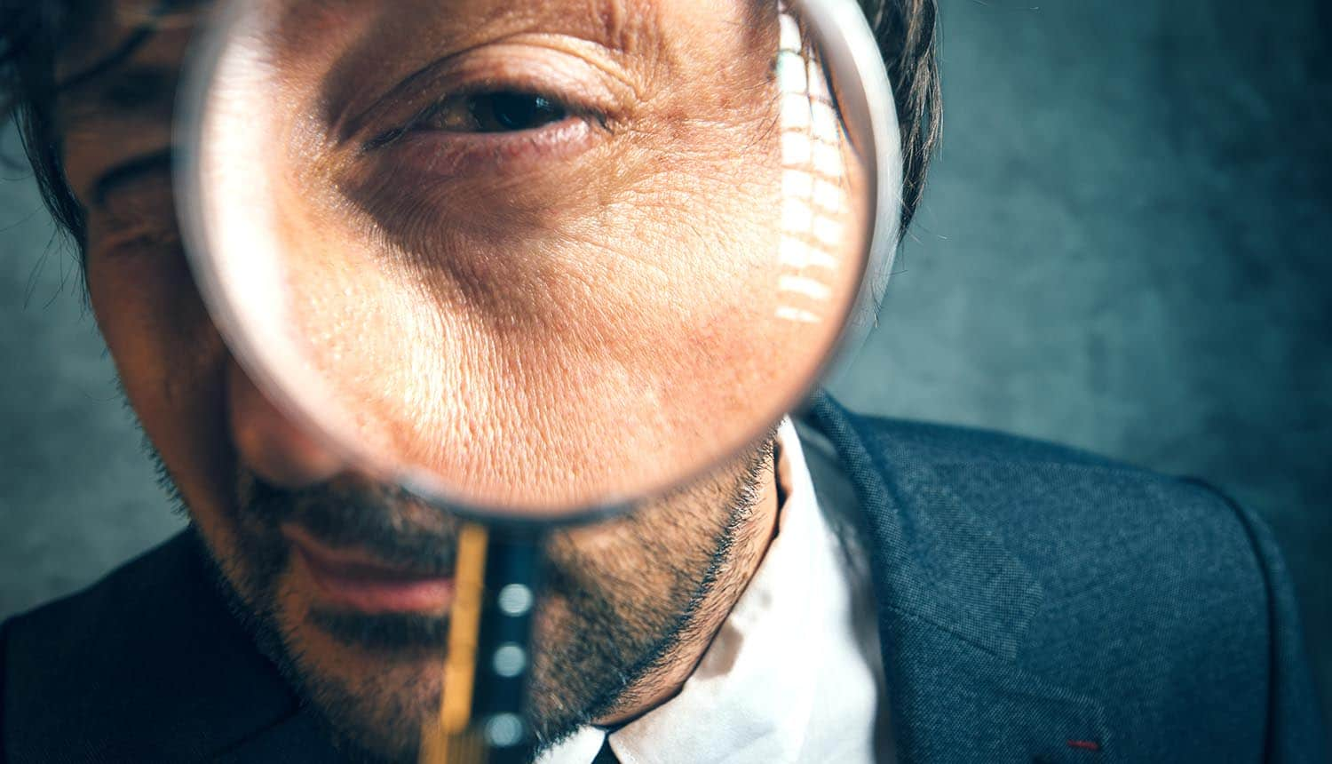 Image of man holding magnifying glass signifying executive taking care of business using a security to-do list