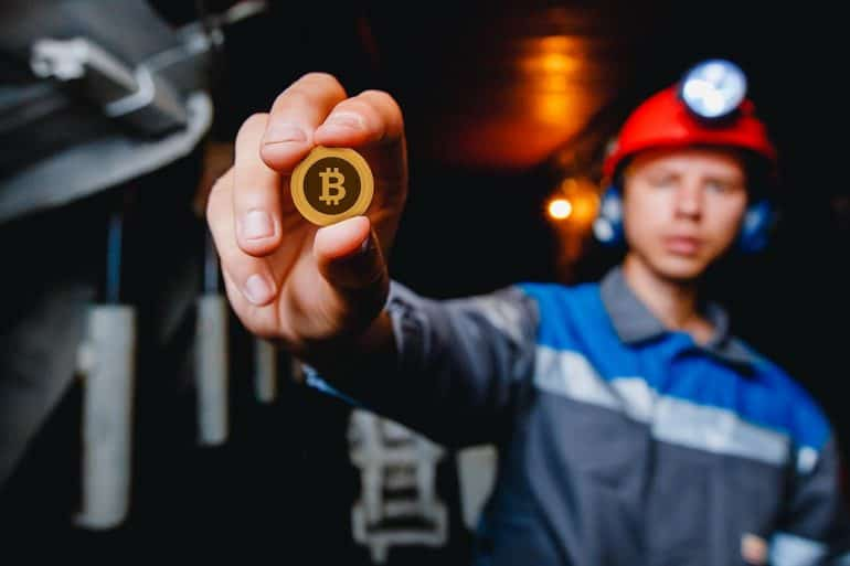 Image of man in hard hat holding a bitcoin signifying cryptocurrency scams using celebrity twitter accounts