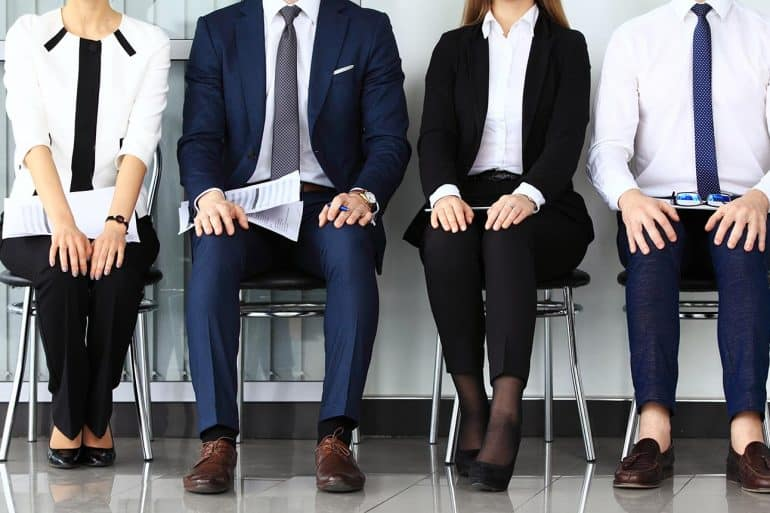 Image of four interview candidates sitting in a row signifying churn in cyber security jobs and how that makes it harder to fight cyber crime