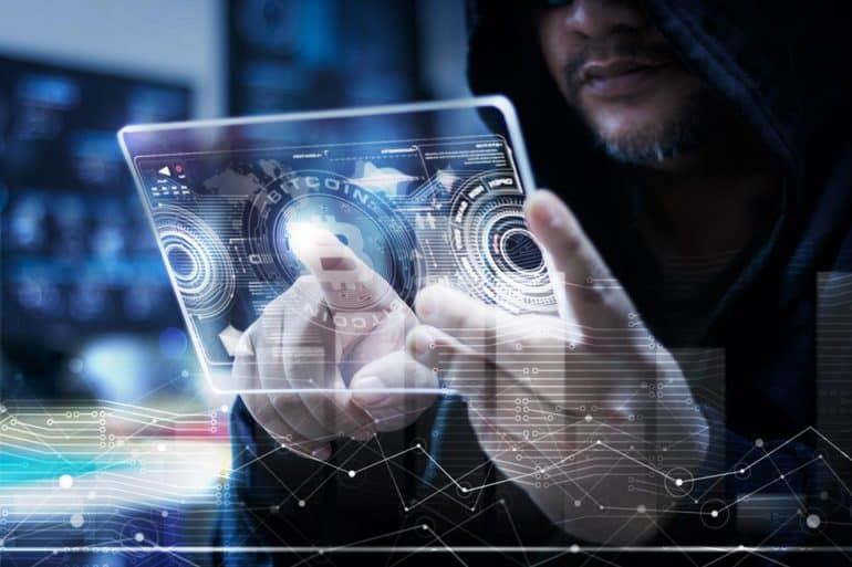 Image of cyber criminal holding a futuristic tablet and getting profits from crypto mining malware